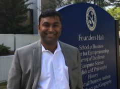 Dr. Hari Rajagopalan stands in front of Founders Hall sign