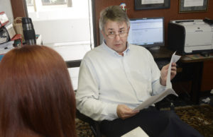 Jon Tuttle talks with a student in his office