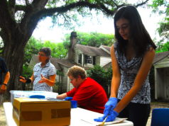 Students and Professors sort through items outside