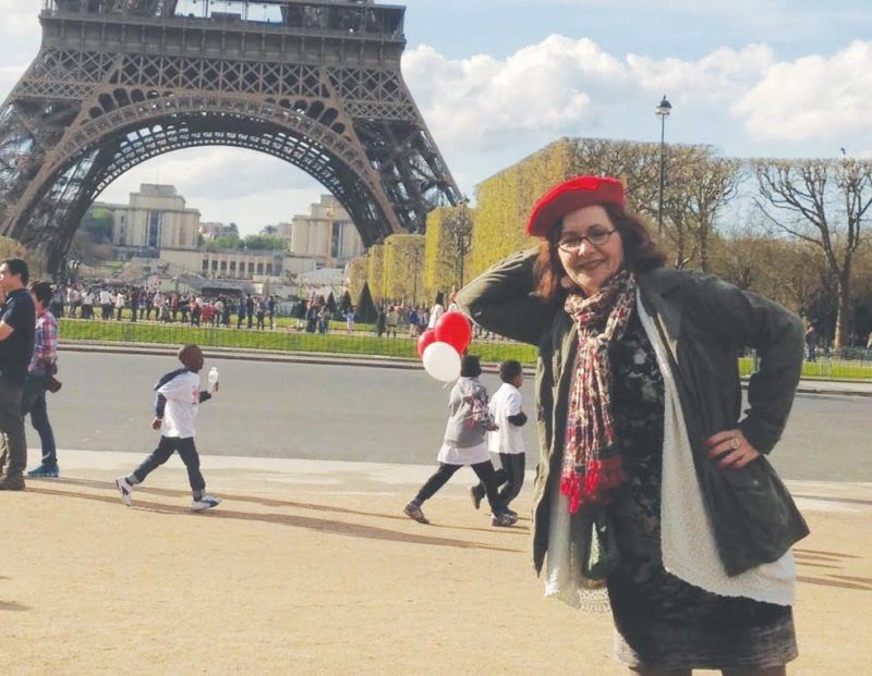 Melaney Mills poses in front of the Eiffel Tower